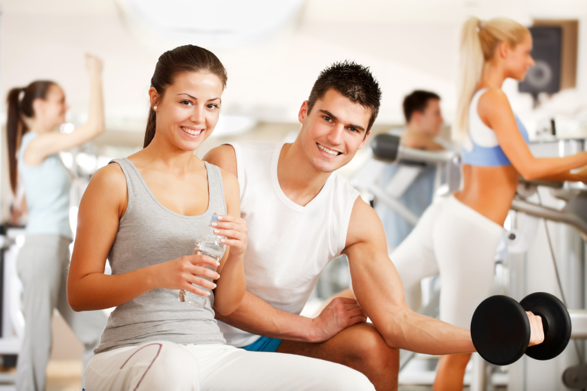 Beautiful couple is smiling.  They have a training at gym. He doing exercise with dumbbells, she drinks a water. Looking at the camera.   [url=http://www.istockphoto.com/search/lightbox/9786766][img]http://img255.imageshack.us/img255/3431/sportt.jpg[/img][/url]